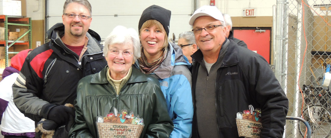 """C.I.A.C.O. members, families and friends gather to assemble """"Baskets of Love"""" - crates with food for people in need."""